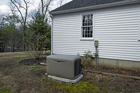 Residential standby generator at the house wall